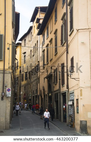 FLORENCE, ITALY - JULY 2016: People walking in a narrow street with historical houses in Florence in Italy