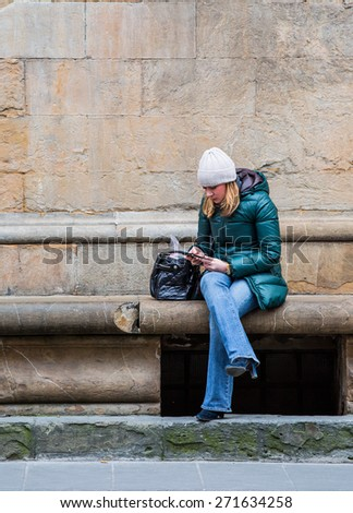 FLORENCE, ITALY - MARCH  15, 2015: Unidentified girl uses her mobile phone  - stock photo