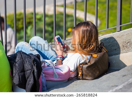 FLORENCE, ITALY - MARCH 13, 2015: Unidentified girl uses her mobile phone in Plaza Michelangelo (Piazzale Michelangelo),Florence, Italy.   - stock photo
