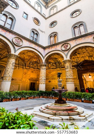 FLORENCE, ITALY - NOVEMBER 22 2016: First courtyard with Putto with Dolphin by Verrocchio in middle, and frescoes of Austrian cities on wall by Vasari. Palazzo Vecchio is town hall.