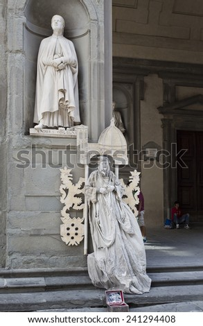 Florence, Italy - September 2014 Living statue street busker stays immobile in front of a real marble statue. September 2, 2014 in Florence, Italy. - stock photo