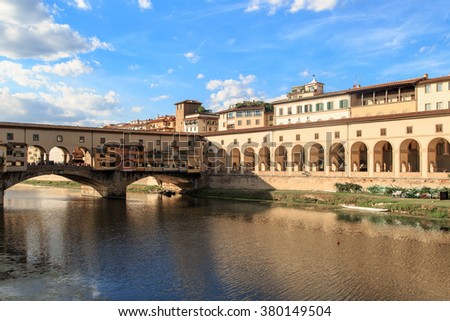 FLORENCE, ITALY - SEPTEMBER 22, 2015 : View of Vecchio Bridge on Arno river, with old buildings around in Florence, on cloudy blue sky background.