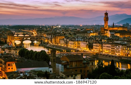 Florence, Italy - skyline view over Arno river with Ponte Vecchio and Palazzo Vecchio at sunset - stock photo
