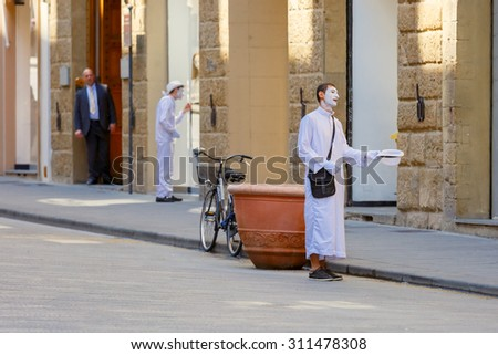 Florence, Tuscany, Italy - May 19, 2015: Street actors in a white dress, gloves, hat and a white mask of a clown near on the street in Florence