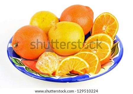 Florida Citrus known as Honeybell or Tangelo is an extremely juicy hybrid citrus fruit.  Colorful plate contains Oranges and tangerines, some peeled and some not.