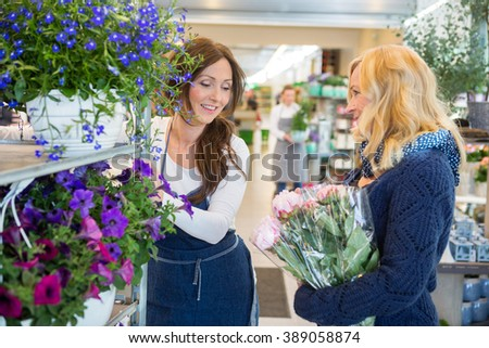 Florist Assisting Customer In Buying Flowers - stock photo