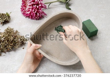 Florist at work: how to make simple floral arrangement with pink chrysanthemum flower and moss. Step by step, tutorial.  - stock photo