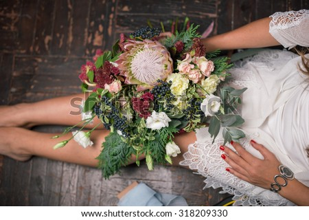 Florist at work: pretty young blond woman holds fashion modern bouquet of different flowers