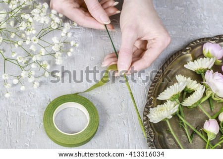 Florist at work. Steps of making wedding wreath with pink rose, ranunculus and white chrysanthemum.