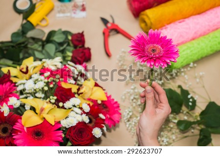 Florist at work. Woman making bouquet of flowers. One gerbera in Focus