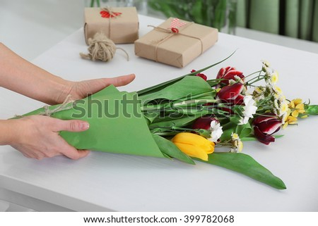 Florist at work: woman making bouquet of fresh flowers. - stock photo