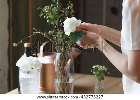 Florist at work: woman making floral composition of different flowers