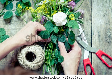 Florist at work. Woman making  floral decorations with retro filter - stock photo