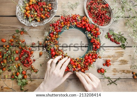 Florist at work: woman making rose hip and hawthorn wreath - stock photo