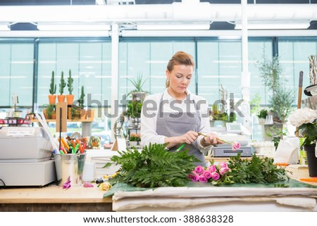 Florist Cutting Stem On Rose At Counter In Flower Shop - stock photo