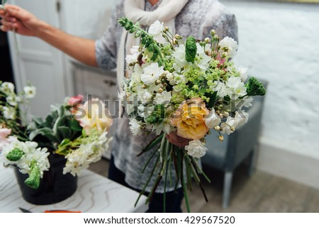 Florist finishing beautiful and rich spring flower arrangement
