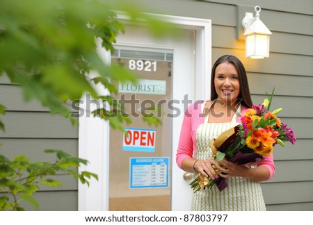 Florist in front of shop with flowers - stock photo