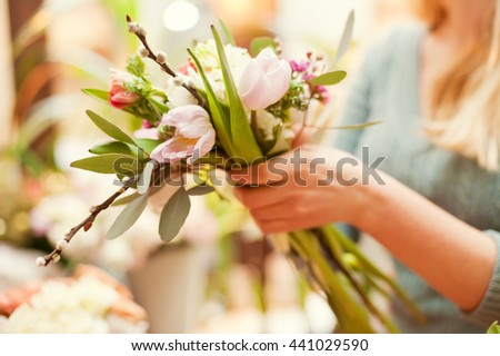 florist making bouquet of ranunculus, tulips and anemone