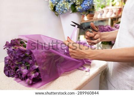 Florist scissors cuts the ribbon on the bouquet - stock photo