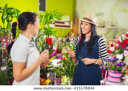 Florist serves female customer in buying flowers at store. Selective focus - stock photo