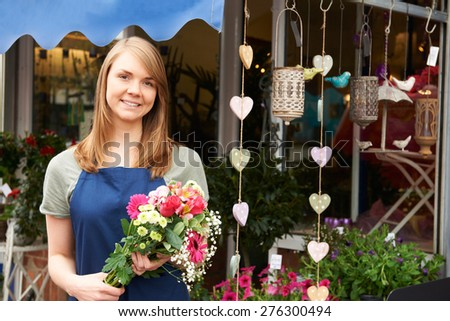 Florist Standing Outside Shop With Bunch Of Flowers - stock photo
