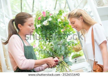 Florist trimming stems of flowers for customer - stock photo