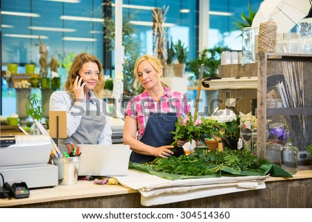 Florist using mobile phone while colleague making bouquet at counter in flower shop - stock photo