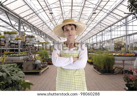 florist with hat in greenhouse - stock photo