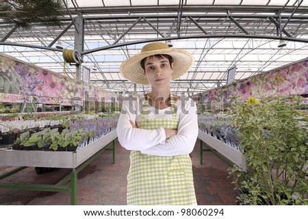 florist with hat in greenhouse among flowers - stock photo