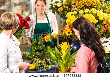 Florist woman preparing bouquet customers flower shop market happy - stock photo