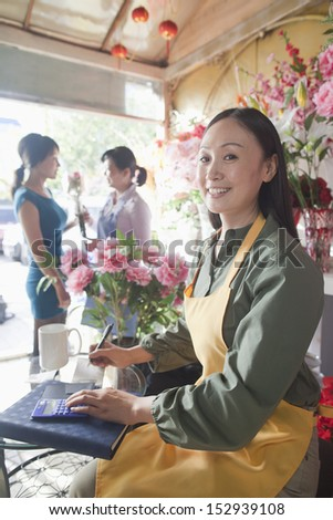 Florist Working In Flower Shop - stock photo