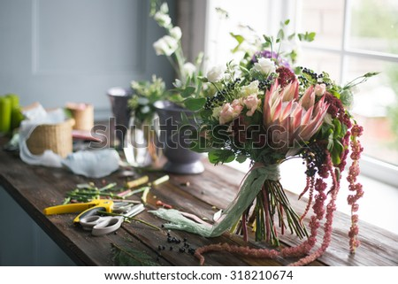 Florist workplace: flowers and accessories on a vintage wooden table. soft focus
