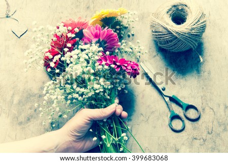 Florist workplace: flowers and accessories. Toned photo - stock photo