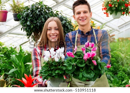 Florists couple at work. Girl and guybholding pots with beautiful violets and smiling
