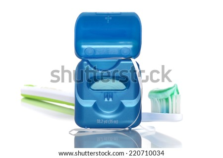floss and toothbrush with toothpaste gel isolated on white background