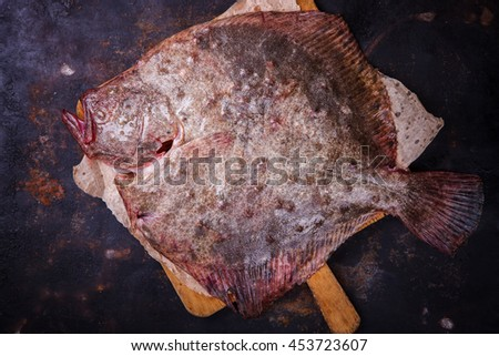 Flounder raw fish on a dark background.selective focus.