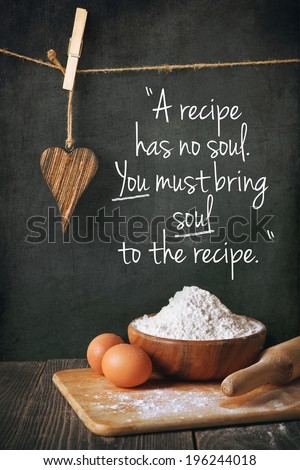 Flour and eggs on a blackboard background as part of a recipe.  Written phrase. - stock photo