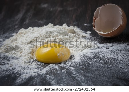 Flour and eggs on a wooden table, selective focus