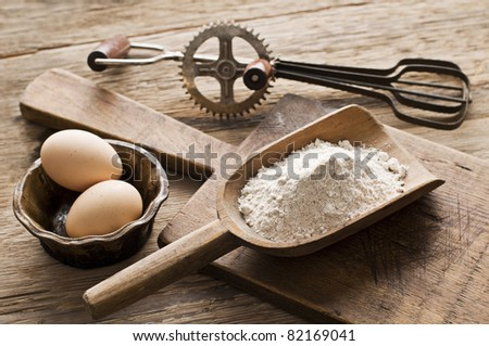 Flour and eggs on wooden background - vintage - stock photo
