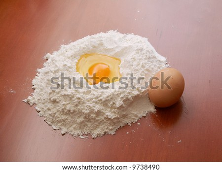 Flour and eggs on wooden table - stock photo