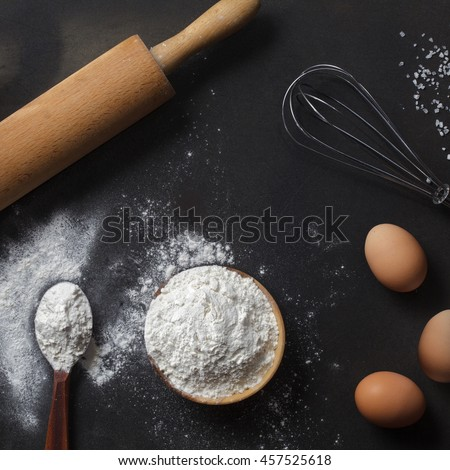 flour and ingredients on black table - stock photo