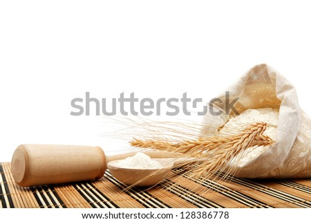 Flour and wheat grain with wooden spoon on a wooden table. - stock photo