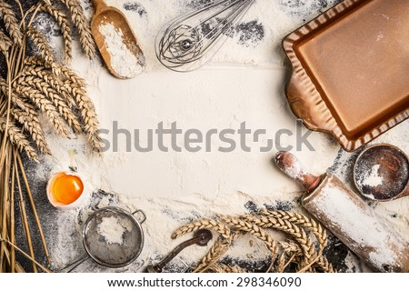 flour baking background with raw egg, rolling pin, wheat ear and rustic bake pan. Top view - stock photo