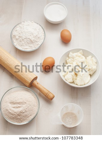 Flour (bread and whole grain) with eggs, ricotta cheese and rolling pin - stock photo