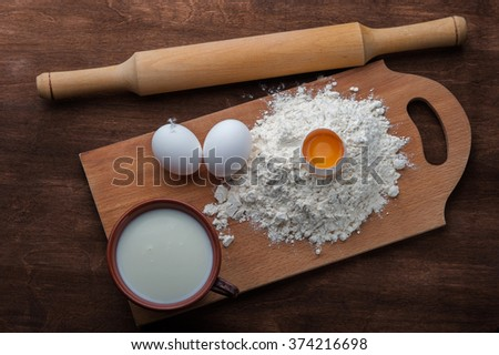 Flour , eggs and milk on dark wooden background. Top view - stock photo