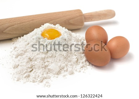 flour, eggs and rolling pin on white background - stock photo