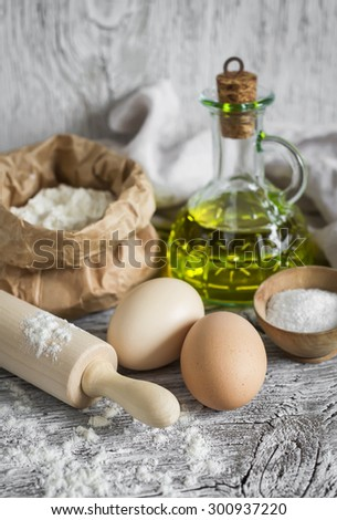 flour, eggs, olive oil - ingredients to prepare the dough for pasta on a light wooden surface - stock photo