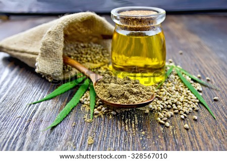 Flour hemp in a wooden spoon, hemp seed in a bag and on the table, hemp oil in a glass jar, hemp leaves on the background of wooden boards - stock photo