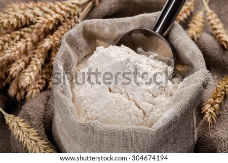 Flour in a bag on the table and spikelets. - stock photo