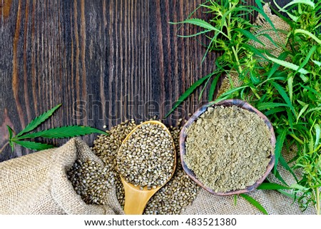 Flour in a bowl and hemp seeds in a spoon, green twigs of cannabis on sackcloth background on wooden board